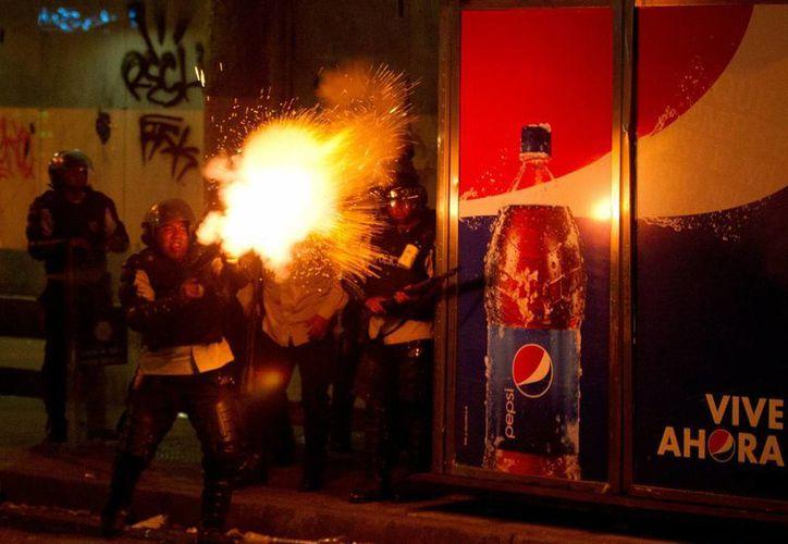 Un policía Nacional Bolivariana dispara gas lacrimógeno a manifestantes contra el gobierno durante los enfrentamientos en Caracas, Venezuela. (Agencias)