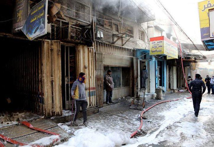 Curiosos pasan cerca de los comercios en donde explotó una de las bombas que sacudieron ayer la capital de Irak. (Agencias)