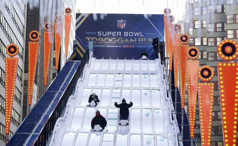 Varios aficionados se divierten en un tobogán instalado en Times Square con motivo de la disputa de la 48 Super Bowl de la NFL. (EFE)