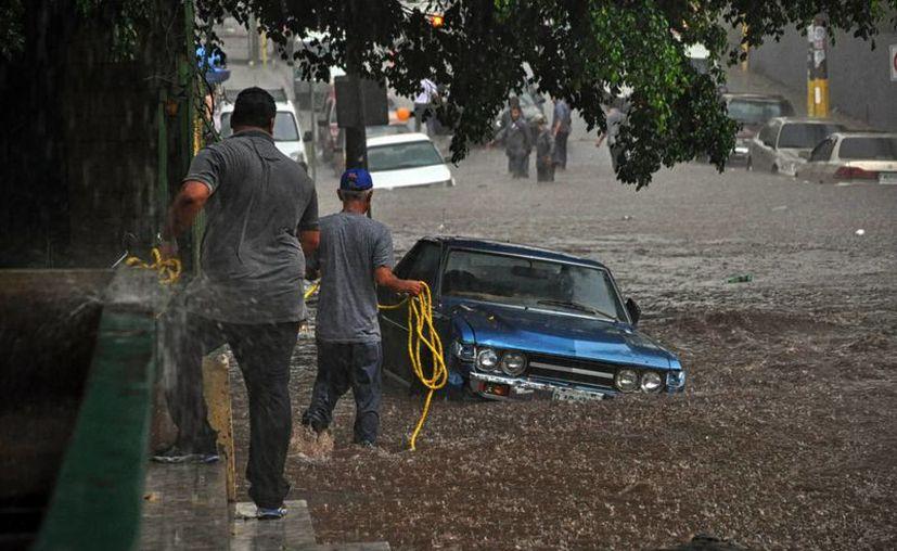 Un grupo de hombres trata de sacar un vehículo atrapado en una inundación debido a una fuerte lluvia en Tegucigalpa, Honduras. (Archivo/EFE)