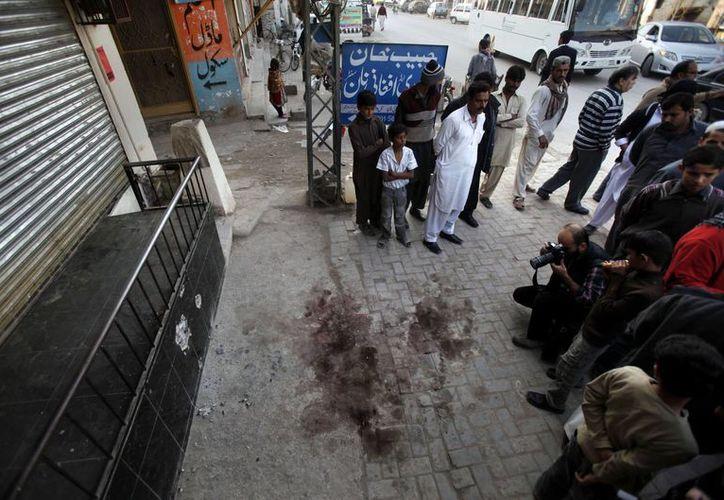 Residentes locales y periodistas se reúnen en el lugar donde fue asesinado Nasiruddin Haqqani. (Agencias)