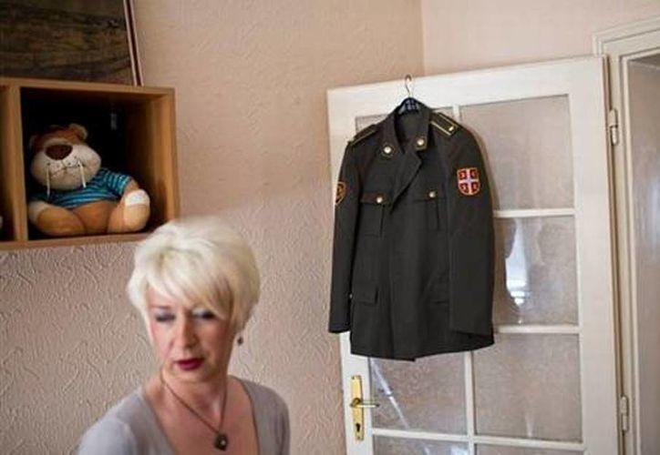 Helena posa para una foto en la casa de un amigo en Belgrado. Dentrás suyo se ve el uniforme que lució cuando era mayor del ejército serbio, antes de iniciar un proceso de cambio de sexo, de hombre a mujer. (AP Photo/Marko Drobnjakovic)
