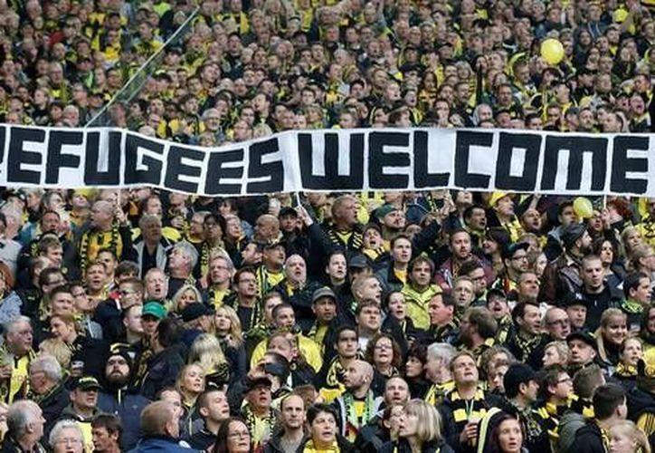 En imagen, aficionados del Borussia Dortmund le dan la bienvenida a los refugiados que llegaron a Alemania durante el fin de semana. Esta jornada la Bundesliga se unirá para emitir un mensaje de apoyo a los migrantes durante sus partidos (Archivo AP)
