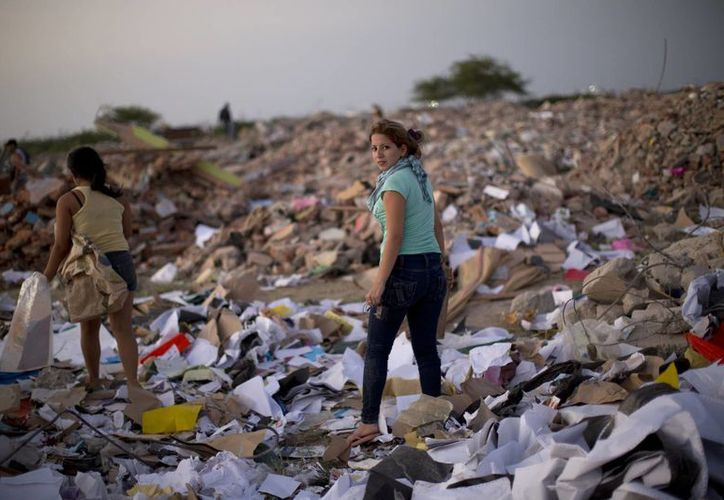 Mujeres buscan materiales reciclables en un campo lleno de los escombros que dejó el terremoto en Manta, Ecuador. (Agencias)