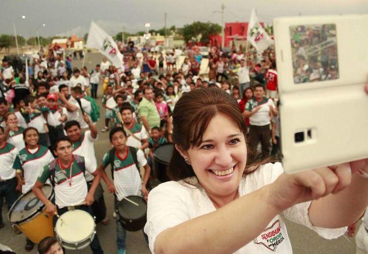 Celia Rivas, candidata del PRI a diputada por el VII Distrito, se toma una selfie con jóvenes en el Paseo Verde. (SIPSE)