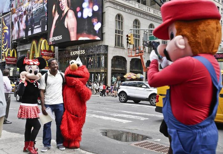 Personas vestidas como Elmo, Mimí y Mario Bross se toman fotos con turistas en Times Square, varios han sido denunciados por agredir a quienes no les pagan el dinero que piden. (AP)