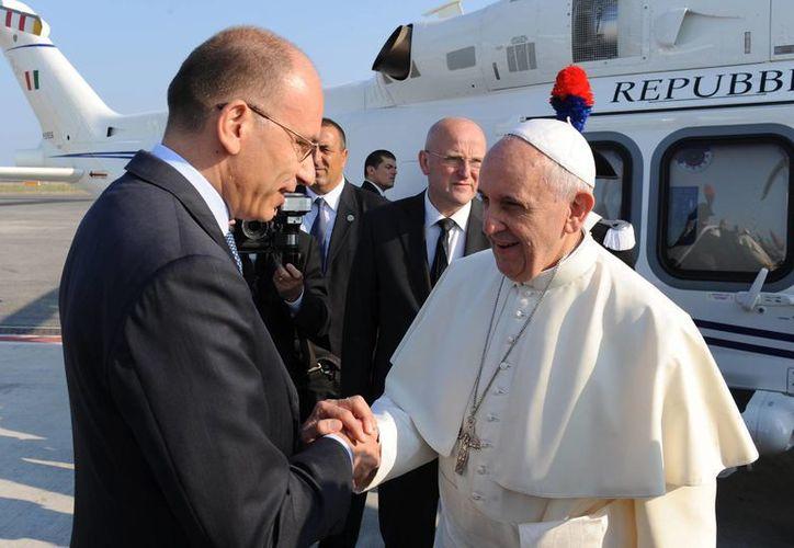 El Papa saluda al premier Enrico Letta en el aeropuerto internacional Leonardo Da Vinci en Roma. (Agencias)
