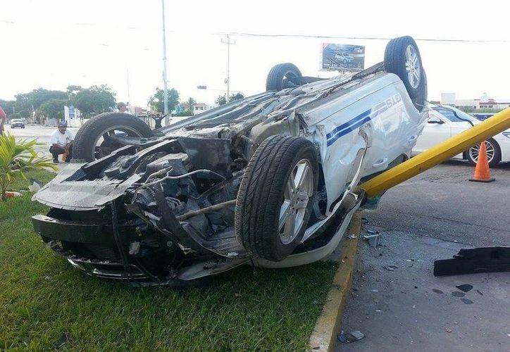 El Avenger que volcó en la Prolongación de Paseo de Montejo dañó a otros tres vehículos estacionados y derribó un semáforo. (Milenio Novedades)