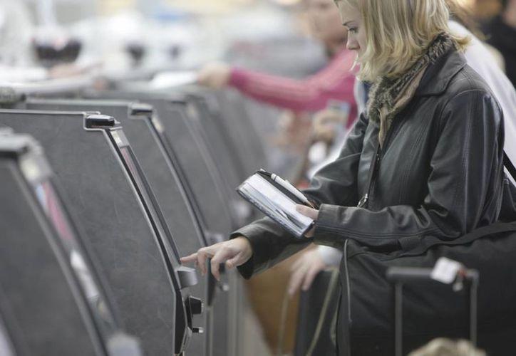 Una pasajera reserva su lugar para un vuelo de American Airlines en el aeropuerto internacional Lambert de San Luis. (Agencias)