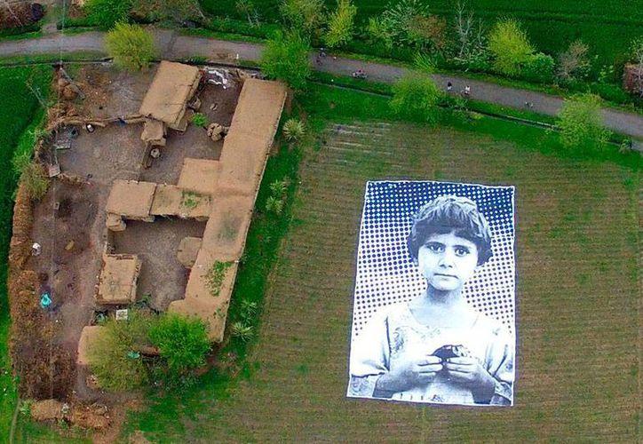En Pakistán, artistas colocaron fotos de una niña que perdió a sus padres y hermanos en un ataque de drones. Buscan inhibir el uso de esta 'herramienta' de guerra. (Efe)