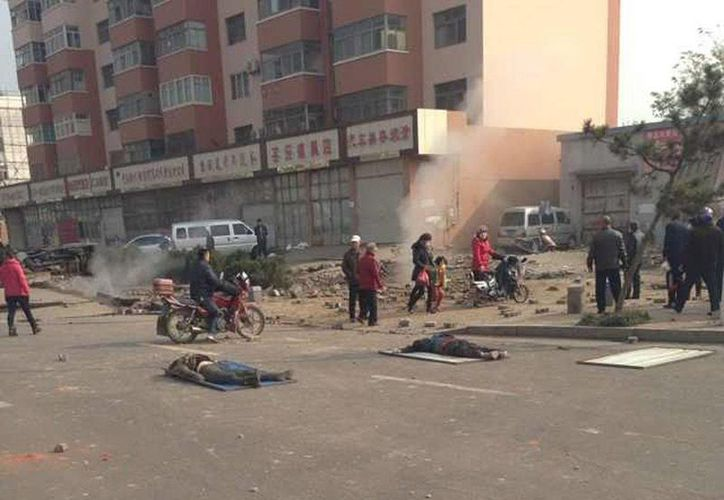 Dos cadáveres yacen en el suelo tras la explosión de un oleoducto en la ciudad costera de Qingdao. (EFE)