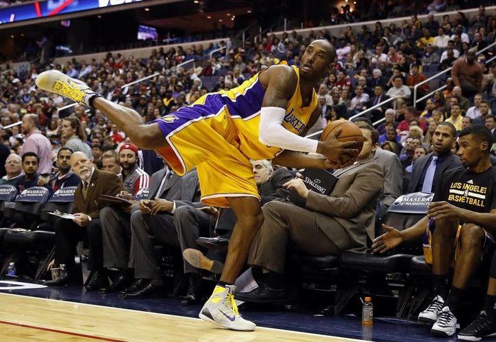 Kobe Bryant trata de mantener el equilibrio en partido en el que Wizards venció a Lakers. (Foto: AP)