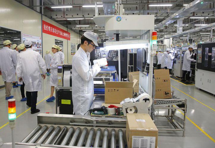 Un obrero trabaja en una línea de producción de teléfonos celulares en la fábrica de Huawei en Dongguan, China. (Foto AP/Kin Cheung, Archivo)