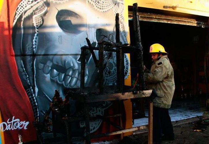 Un local comercial que vende artículos de la Santa Muerte sufrió daños en parte de las paredes y en los productos, a causa del fuego. (Jorge Acosta/SIPSE)