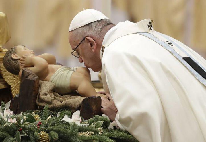 El Papa Francisco besa una estatua del Divino Infante mientras celebra una misa de Año Nuevo en la Basílica de San Pedro en el Vaticano, el domingo 1 de enero de 2017. (AP Photo/Andrew Medichini)