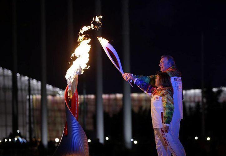 Los rusos Irina Rodnina y Vladislav Tretyak durante el encendido del fuego olímpico en Sochi. (Agencias)
