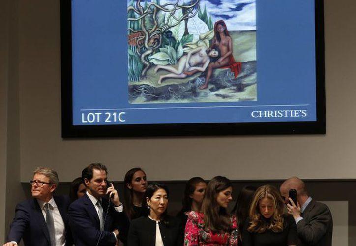 El cuadro 'Dos desnudos en el bosque (La tierra misma)' de Frida Kahlo aparece en una pantalla de video durante la subasta que se realizó en Nueva York. (Agencias)