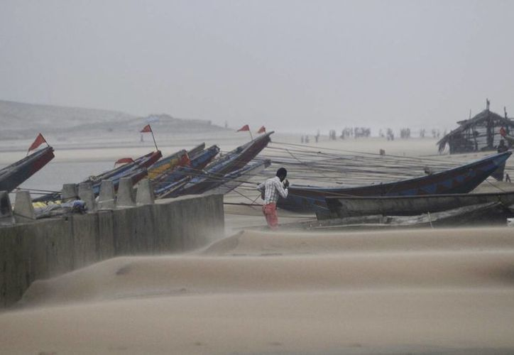 Un pescador camina cerca de barcos de pesca anclados, debido a los fuertes vientos del poderoso ciclón que golpeó la costa de la Bahía de Bengala en Gopalpur, Orissa, cerca de 285 kilómetros (178 millas) al noreste de Visakhapatnam, India. (Agencias)
