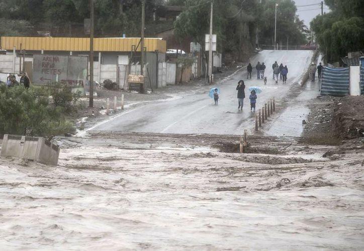 Residentes observan la crecida del río Copiapó, en Copiapó, Chile, el 25 de marzo de 2015. Las autoridades han evacuado a miles de personas de las zonas inundadas. (Foto AP/Aton Chile)
