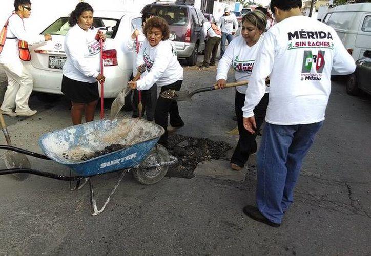 Los funcionarios priistas durante el bacheo en calles de la colonia Pensiones de Mérida. (SIPSE)