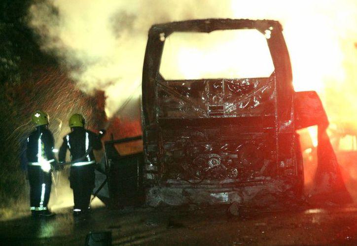 Bomberos intentan apagar el fuego en los vehículos involucrados en un accidente automovilismo en el estado de Puebla. (EFE)