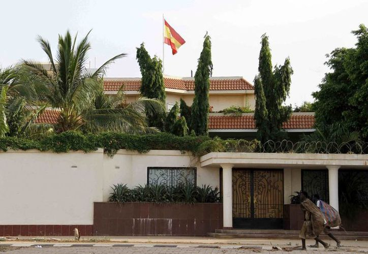 Dos hombres caminan junto a la casa del jefe de la sección de visados español que murió hoy apuñalado en Jartum, Sudán. (EFE)