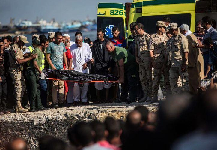 Decenas de migrantes duermen en la costa esperando que las autoridades encuentren los cuerpos de sus familiares. (AP)