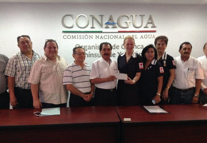 La delegada en Yucatán de la Cruz Roja Mexicana, Michelle Byrne, recibe el cheque con la cantidad que trabajadores de la Conagua en la entidad recolectaron a favor de la institución. (Cortesía)