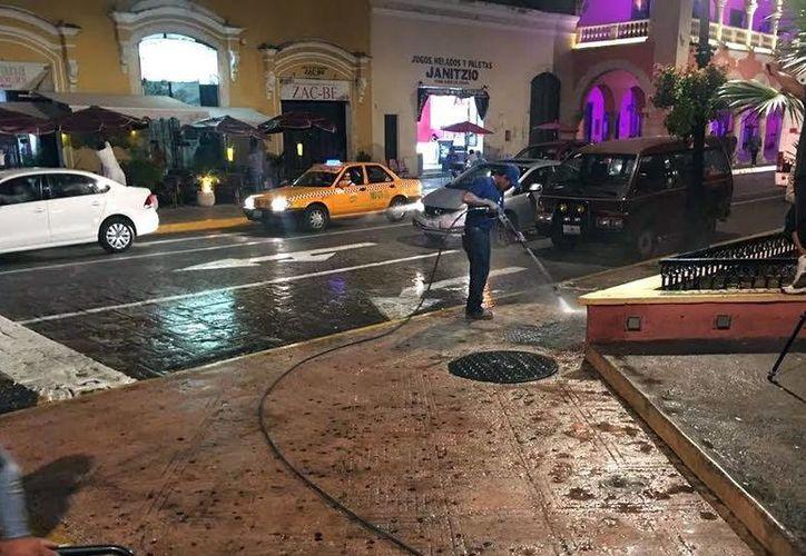 Con líquidos a presión quitan chicles en la Plaza Grande de Mérida. (Milenio Novedades)