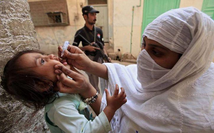 Una trabajadora vacuna contra la polio a una niña, en Peshawar, Pakistán. (EFE)
