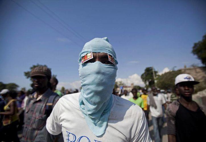 Un hombre enmascarado asiste a una protesta para exigir la renuncia del presidente Michel Martelly en Port-au-Prince, Haití. (Agencias)