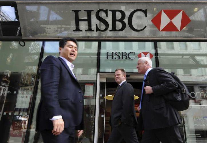 Tres hombres pasan junto a una sucursal del banco británico HSBC en Londres, Inglaterra. (EFE/Archivo)