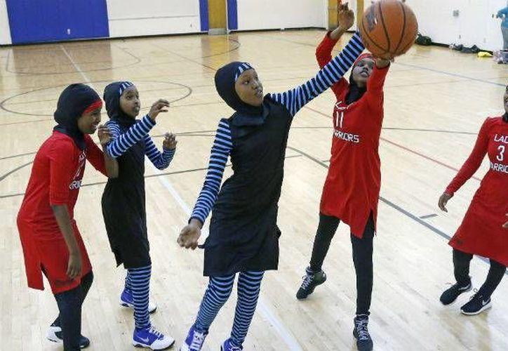 Las niñas diseñan su propia ropa deportiva sensible a su cultura que cubre sus brazos, piernas, cabello y cuello, preservando la modestia requerida por su religión. En la foto; El equipo Lady Warriors(Rojo) se enfrentan contra sus mismas compañeras en un partido amistoso. (AP)