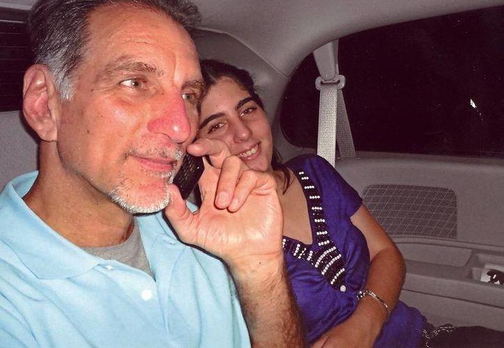 El agente cubano convicto René González habla por teléfono, acompañado por su hija Ivette.Gonzalez. (Agencias)