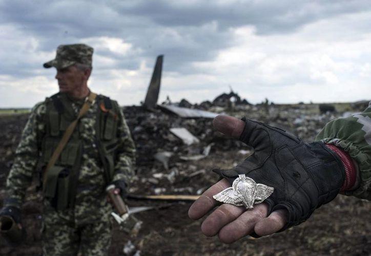 Un miliciano separatista prorruso muestra un emblema de los paracaidistas, teniendo como fondo el sitio donde cayó el avión de transporte de tropas II-76, cerca de aeropuerto de la ciudad de Lugansk. (Foto: AP)