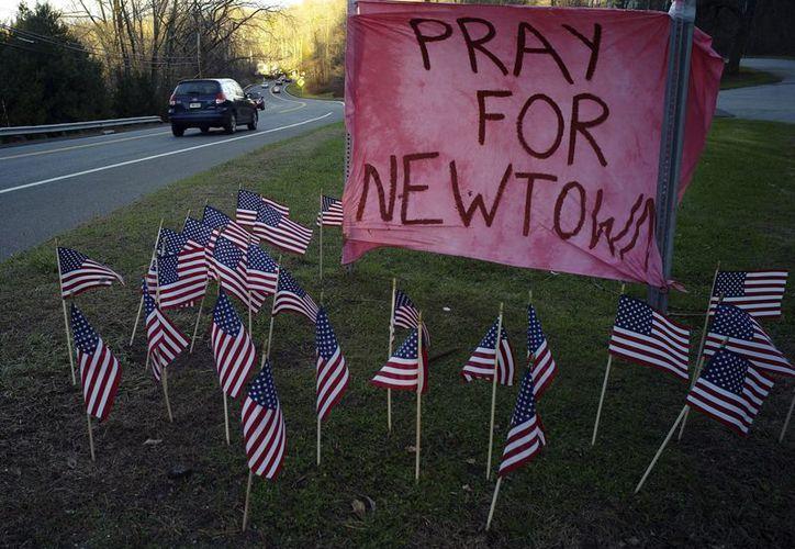 """Banderas y un cartel en el que se lee """"oren por Newtown"""" permanece en una colina en dirección a esa localidad de Connecticut. (EFE)"""