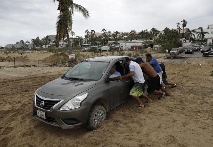Un grupo de personas ayudan a un turista a mover su coche después de que se quedó atascado en la arena, tras el paso del huracán Newton en Cabo San Lucas, México. (AP/Eduardo Verdugo)