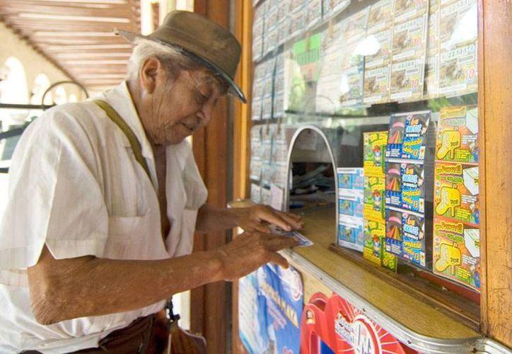 A pesar de la baja en ventas de billetes de la Lotería Nacional, en Yucatán hay clientes cautivos del 'gordo'. Muchos yucatecos prefieren 'juegos' que den dinero 'más rápido' como 'Tris' o 'Chispazo'. (Milenio Novedades)