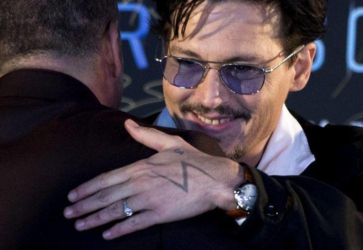 Al preguntarle sobre su compromiso con la actriz Amber Heard, Johnny Depp levantó la mano izquierda y respondió: 'El hecho de que llevo un aro de mujer en el dedo probablemente me delata'. (Agencias)