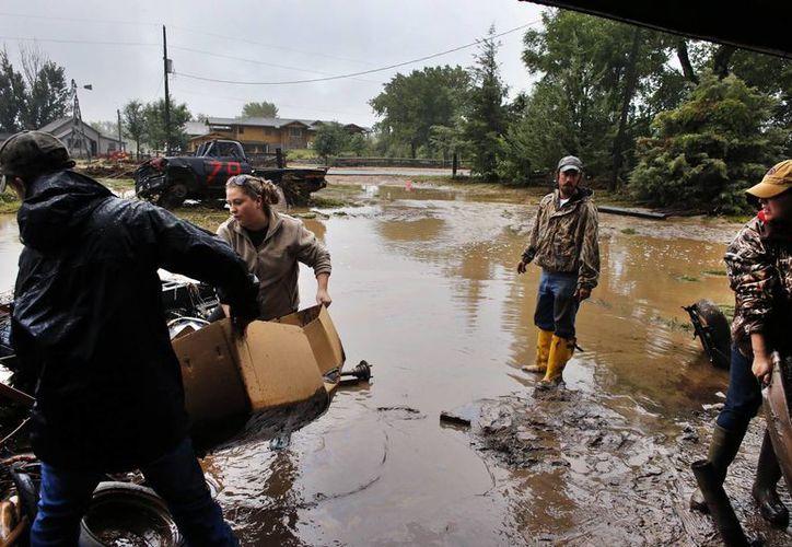 Ansiosos residentes y dueños de negocios se apresuraron a limpiar y despejar lo que podían salvar. (Agencias)