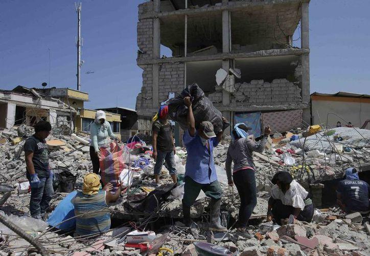 Los residentes tratan de recuperar algunas de sus pertenencias enterradas en los escombros en un bloque de barrio que fue destruido por el terremoto en Pedernales, Ecuador. (Agencias)