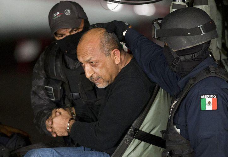 """En esta fotografía de archivo del 27 de febrero de 2015, la policía federal mexicana escolta a Servando """"La Tuta"""" Gómez, líder del cártel de los Caballeros Templarios, dentro de un helicóptero en un hangar federal en la Ciudad de México. (AP Foto/Eduardo Verdugo, archivo)"""