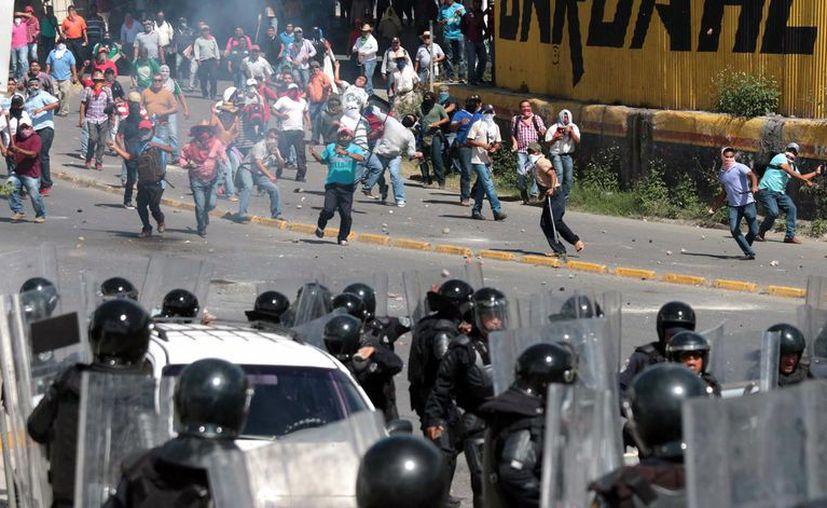Los maestros de la CETEG lanzaron piedras y bombas molotov a los efectivos policiales. (EFE)