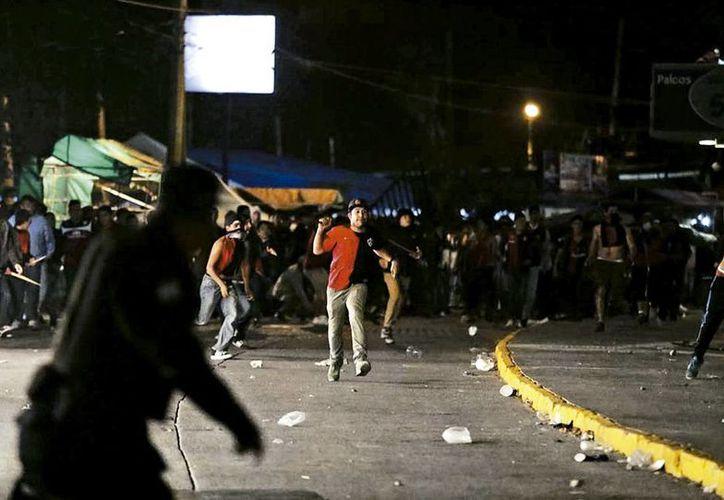 Barristas se enfrentan a la policía de Guadalajara. Tras la eliminación del Atlas en cuartos de final sobrevino la agresión de los aficionados rojinegros.  (Milenio)