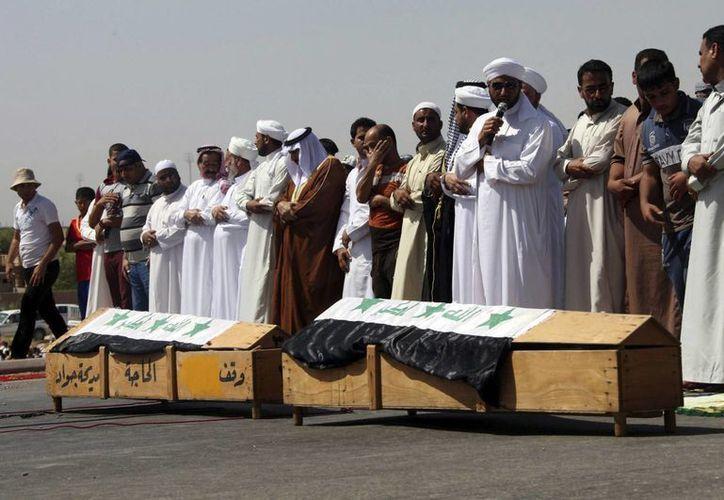 Sunitas portan los ataúdes de dos 'hermanos' suyos muertos tras un un ataque en Baghdad. (EFE)