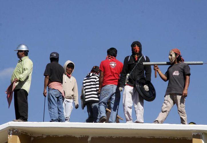 Padres de familia atrincherados en la escuela primaria 'Hermanos Flores Magón', en Oaxaca, en noviembre, en el marco de la violencia que ha imperado en los últimos meses en escuelas de ese estado. (Notimex)