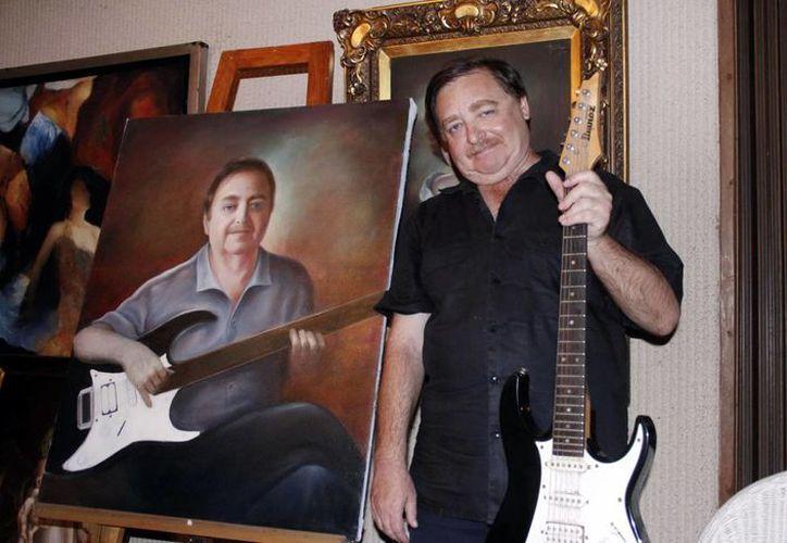 Torre Aguilar posa con su guitarra y un cuadro que pintó su padre. (SIPSE)
