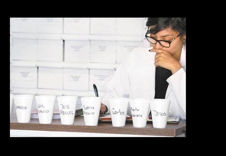 Una doctora prepara las dosis para los pacientes, cuyos nombres están escritos en los vasos. (Jorge Carballo/Milenio)
