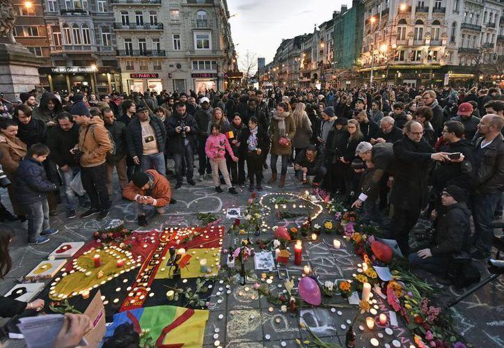 La gente lleva flores y velas a la plaza de la Bolsa en el centro de Bruselas, tras los ataques en el aeropuerto y el Metro. (Agencias)