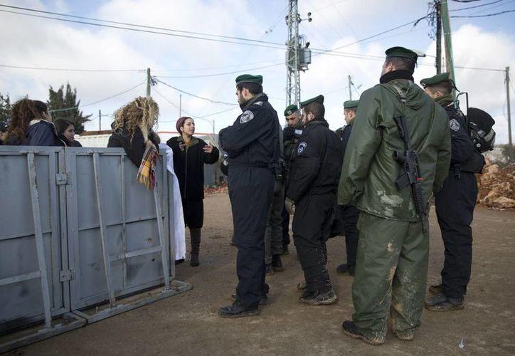 Colonos hablan con la policía israelí en el puesto de Amona. El ejército emitió una orden de evacuación en la víspera advirtiendo a los residentes que tienen 48 horas para desalojar la zona. (AP/Oded Balilty)